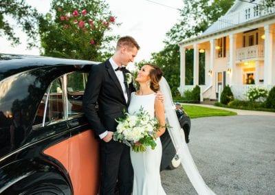 newlyweds posing by car