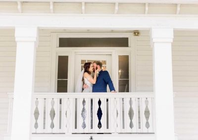 Bride and Groom kiss on balcony at Camelot Manor